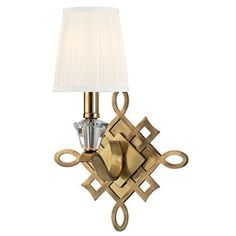 The Fowler wall sconce in aged brass has a stunning scrollwork backplate. A single light with a gathered silk shade and a cut crystal bead at the base. This modern light would be fantastic by the bedside.