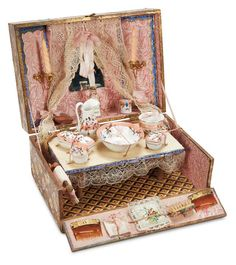 "French toilette for poupée, circa 1894, in unusual original presentation box covered with lithographed papers, labeled ""Toilette"" in gilt letters, that forms a toilette table with mirror flanked by gilt ormolu candle holders. Nine-piece service arranged upon the table top along with various combs, soaps, silk sachets, brushes, and other articles."