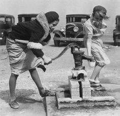 Two teen girls pump water from a well in the middle of a dust storm and still look fabulous.
