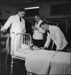 A male nurse at Runwell Hospital inserts a gag into a patient's mouth as the doctor (left) prepares to begin Convulsant Therapy treatment. A second male nurse prepares the electrodes .