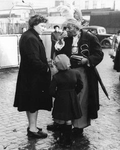 Ras Prince Monolulu, a well-known horse tipster, at Mile End Market talking to a woman and a young girl, 1947. Born as Peter Mackay in 1881 in St. Croix in the American Virgin Islands, the tipster came over to Britain in the early 1900s and soon became one of the best-known and flambouyant London showmen. Until his death in 1965 he was probably the most famous black man in Britain.   Artist/Photographer/Maker Bob Collins   Date 1947 AD - 1947 AD: