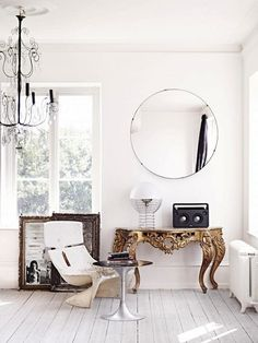 A Swedish reading nook with a chandelier, a vintage mod chair, and a large round mirror