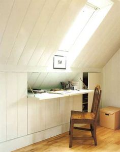 A fold-down desk and skylight for added headroom carve a home office out of this sloped-ceiling attic room.