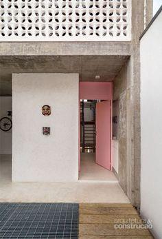 Pintada de rosa (esmalte acetinado da Suvinil em tom feito sob encomenda), a porta metálica quebra a frieza do concreto, que marca praticamente todo o projeto. Projeto de Maurício Takahashi.