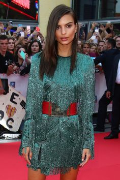 Emily Ratajkowski with glowy makeup and a green tassled dress