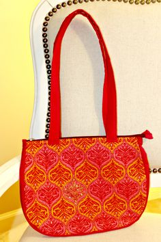 Handmade fashionable purses and bags. Dhara Bags are handmade by a female tailor workshop in India, and proceeds from sales go to providing nutritious meals to the homeless. Available here- http://www.dharabags.com. Just like flowers, this bag fashions bright pink and orange heritage Indian print on cotton.