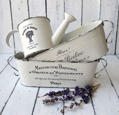 White metal containers, painted with, with French graphics added. No tutorial but she sells the directions I think.  Dreams Factory: vintage looking metal vessels