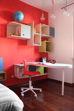 Angolo studio di una cameretta pensato con librerie a giorno e chiuse e un piano scrivania che può essere usato da entrambi i lati.