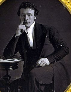 1840s: This fashionable Victorian showcases the high collar that was so common during the 1840's and has the low cut vest and long frock coat to complete his outfit. The sleeve on his frock coat is very tightly tailored and appears to have extra decorative buttons at the wrist. His hair is casually combed slightly forward and over his ears.