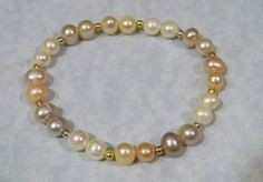 Stretch bracelet with 8mm white, peach and mauve freshwater pearls with 2mm gold, rose gold and platinum clad beads.