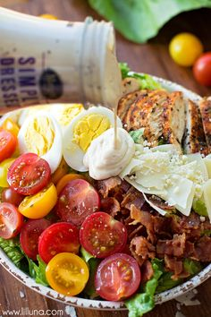 Ultimate Caesar Salad with grilled chicken, croutons, tomatoes, bacon, hard-boiled eggs, Parmesan cheese and tomatoes.