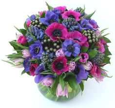 Anemone Surprise! A lime green fish bowl with a stunning arrangement of cerise and blue anemones, blue hyacinth and pink tulips finished with albiflora. #Flowers #MothersDay