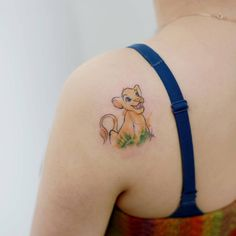 Sketchy Simba tattoo on the left shoulder.
