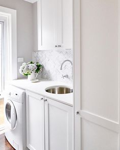 gray laundry rooms Small white laundry room features a front loading washer enclosed beside white shaker cabinets fitted with polished nickel knobs and a white quartz countertop fitt Herringbone Tile Backsplash, Laundry Room Design, Metal Sink, White Laundry Rooms, White Shaker Cabinets, Laundry In Bathroom, Room Design, Herringbone Backsplash, Shaker Doors