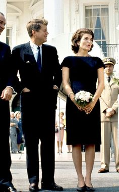 President and Mrs. Kennedy stand in front of the White House, 1961.