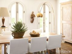 In the dining room, presided over by a 19th-c. carved saint, every object has presence. Custom white oak table. Custom chairs with slipcovers in Christian Liaigre linen. Flos Arco floor lamp, custom finish. - Veranda.com
