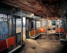 Lori Nix and Kathleen Gerber spent seven months building this minute replica of a New York City subway car. Sprouting weeds and plastered with ironic posters, it sits in a desert. The city's skyline is visible beyond.. Artists' tiny models imagine what a city might look like after humans are long gone.