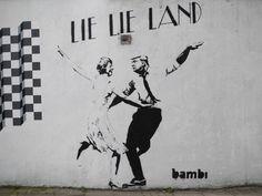 """Un graffito anti-Trump, firmato dalla street artist Bambi è spuntato su un muro del borgo londinese di Islington. Nel murale, in bianco e nero, Theresa May e Donald Trump ballano come nel film """"La La Land"""" al posto degli attori, in odore di Oscar, Emma Stone e Ryan Gosling. Sull'immagine campeggia l…"""