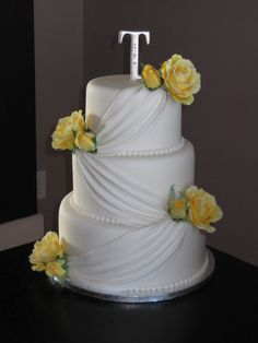 This wedding cake is covered in white fondant.  Draping has been added to give it a simple but elegant look.  Yellow roses were added.