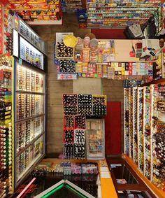 Menno Aden, Untitled (cornershop II), 2011, 120x100 cm    Per scattare queste fotografie il fotografo installa una fotocamera sul soffitto e scatta in remoto, cioè a distanza. L'idea è creare una sorta di estetica da Grande Fratello, dove un occhio onnipresente segue dall'alto i nostri movimenti e la nostra vita.