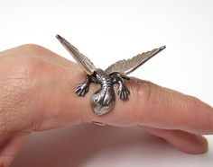 *GOTHIC STEAMPUNK JEWELRY*    This pet dragon just love to hold onto your finger and follow you everywhere. A belly or back rub is always pleasing to. Adorable.    This dragon is made from brass stampings with gorgeous detailed scales and feather wings. This antiqued silver tone brass ring is adjustable to fit onto a 5-10 ring size comfortably. Dragon wing span is 1 3/4' inch (45 mm) wide.     I can pre-size this for you. If you need a printable cut out chart to find your ring size, just let…