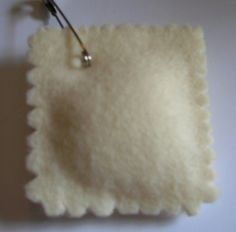 Ravioli swap using beige felt, scalloped scissors, stuffing and a safety pin