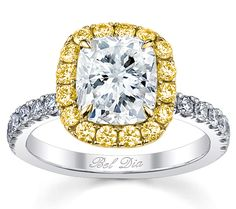 The center cushion diamond is prominently displayed in a halo made up of stunning yellow gold and brightly shining fancy yellow diamonds.