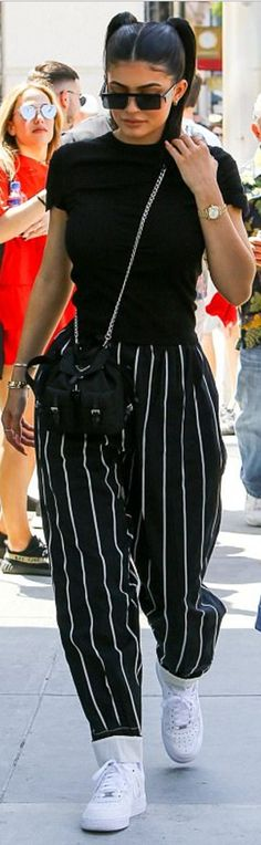 Who made Kylie Jenner's sunglasses, chain bag, stripe pants, black top, and white sneakers?