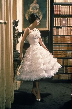 Model is wearing a frothy, tiered party dress by Chanel, 1960
