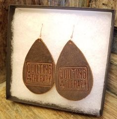 "Now you can show your love of quilting with these light and stylish earrings. Made with dark brown leather and stamped with the ""Quilting Is My Therapy"" logo, they have just a hint of a distressed look. It's the next best thing to actually quilting!"