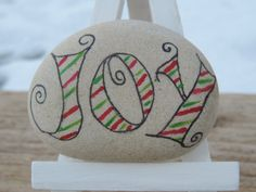 Hand painted, white Lake Erie beach stone with the simple word JOY in fancy font. The fonts are filled in with red and green strips with acrylic paint. This decorative stone measures 2.5 inch by 2 inches and will sit nicely on an easel which comes with this stone. On the back of the