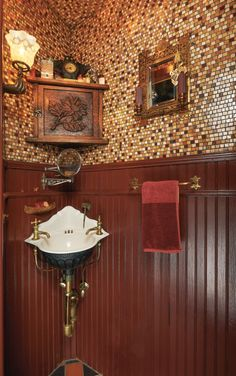 "Nowhere is it more fun to go over the top than in a space-challenged half bath. Here, custom mosaics and Victorian wood wainscot join a salvaged period corner sink and gaslight-era ""hand"" sconces."