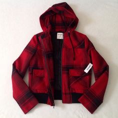 """NWT Old Navy red plaid wool coat This Old Navy red plaid jacket is great for the fall. It zips up the front, and has two front pockets. Actual color may vary slightly from pictures.   Materials: Shell: 62% wool, 21% polyester, 17% rayon Lining: 66% polyester, 33% cotton Original price: $59.50 Condition: New with tags, initials are written on the inside tag as shown  Measurements: Shoulders: 15.5"""" Bust: 18"""" Length: 21"""" (shoulder to hem) Sleeve length: 24""""  🎀 No trades 🎀 No holds 🎀No…"""