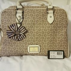 Guess bowling bag style purse Brown and cream Guess purse. Outside is immaculate. Inside could be better.  I let my daughter borrow it for school and she let a green pen leak on the inside :(.  Luckily it didn't not leak to the outside. Tons of room on the inside!! Guess Bags Shoulder Bags