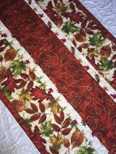 Fall Autumn Leaves Table Runner Quilt featuring leaves in beautiful Fall colors. A lovely, decorative addition to your Fall or Thanksgiving Table. Measures 52 Long x 15.75 Wide.  Quilted with a matching thread in a meandering stitch. Warm and Natural Batting is sandwiched in between layers. The matching binding has been doubled and machine stitched to quilt. Reverse side is shown in the last photo.  Spot clean with cold water. Lay flat to dry. Iron, as desired.  Note: This listing is for the…