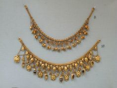 Gold Etruscan strap necklaces from the Tuscan Maremma (6th century BC). The first one of plaited wire and suspended chains, beads, rosettes, acorns, lotus flowers and buds. The second necklace is hung with the heads of a river-god, sirens, flowers, buds, scarabs and settings for onix gems and amber.