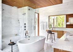 Inspired by the wood often used in boats, a teak ceiling adds a warm quality to the white marble and porcelain tile in the master bathroom. Modern Bathroom, Master Bathroom, Bathroom Ideas, Wall Of Water, Restaurant Icon, Frosted Glass Door, Hanging Cabinet, Built In Bar, Atlanta Homes
