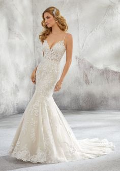 Shop Morilee's Lunetta Wedding Dress. This beautiful spaghetti strap Lunetta wedding dress features stunning beading, embroidery, and appliquès on an intricately designed net gown. Available in white, ivory, and ivory/crème, this v-neck neckline completes this sheath silhouette.