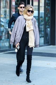 Gigi Hadid in sunglasses, bomber jacket, tan scarf, blue jeans, and black suede boots.