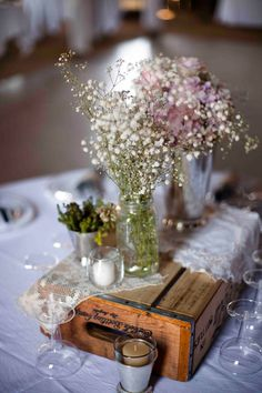 tablescape with bottle box, doilies, votives, and baby's breath in mason jars