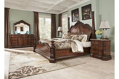 """The Ledelle Poster Bedroom Set from Ashley Furniture HomeStore (AFHS.com). With the traditional dark cherry stain finish flowing beautifully over the elaborately ornate details, the """"Ledelle"""" bedroom collection features rich Ash swirl and Birch veneers along with Asian hardwoods and natural marble parquetry tops on the case pieces to create a sophisticated Old World style."""