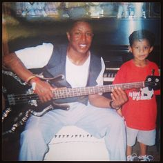 Jermaine playing a guitar with Jermajesty Jackson by his side.