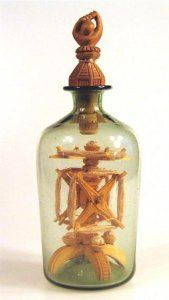 "Folk Art Carving of a Ball in Hand, with a ""Yarn Winder"" in a bottle. Love the folk art hand carved bottle stopper."