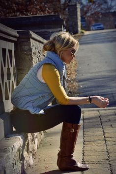 Vest & two tone three quarter sleeve t-shirt.  Denim jeans & brown leather boots.