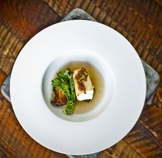 Executive Chef Josh Drage's tasting menus are a thing of farm-to-table beauty. This course features Alaskan halibut, matsutake mushroom and broth, broccoli raabe and caramelized shallot vinaigrette. Photo at The Ranch at Rock Creek, Relais & Châteaux, by Lynn Donaldson.