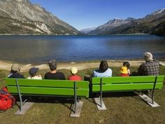 People sitting on green benches at alpine Silser See (lake). Tourist Center, I Want To Travel, Once In A Lifetime, Travel And Tourism, Travel Information, Lonely Planet, West Virginia, Road Trip, Places To Visit