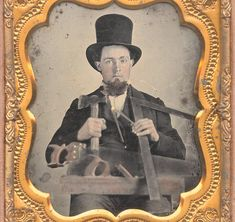 6th plate ambrotype, anonymous American, carpenter with hatchet, compass, square, wood saw & plane.  His skin and parts of the tools have been hand-colored, some gilt has also been applied. Housed in half case.