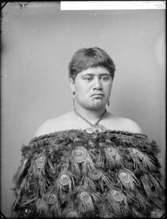 Pare, a young Maori woman with moko (facial tattoo). She is wearing a feather cloak further adorned with peacock feathers. Photograph taken by William Henry Thomas Partington, 1900