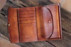 『秋色ハンドメイド2016』イタリアのヌメ革を使用したミドルタイプの二つ折り財布、手染めキャメルブラウンです。長財布と同じくらいの収納力があり。ポケットに入れてもかさばらないサイズが魅力、女性男性共に人気のモデルです。手作りの真鍮製ボタンがポイント。サイズ  14×9.5×2.5…