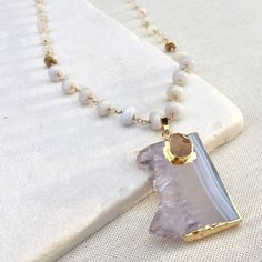 Long Amethyst Drusy Geode Slice Stone Necklace From my handmade Luminous Soul collection. This beautiful amethyst slice has pastel colors that make me excited for spring. There is a small natural orange turquoise cab that contrasts nicely. For the chain, I chose light periwinkle colored lace agate and moonstone beads. All of the links are double wrapped and won't break apart. The delicate gold chain also he links that are soldered shut, so the entire necklace is very strong and you can wear…